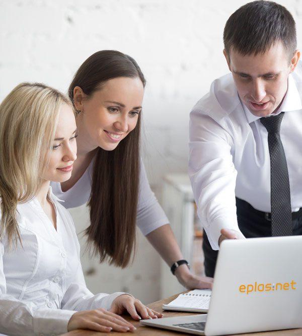 drei Menschen über ein Laptop beugend sich unterhaltend, eplas-Logo auf der Rückseite des Laptops