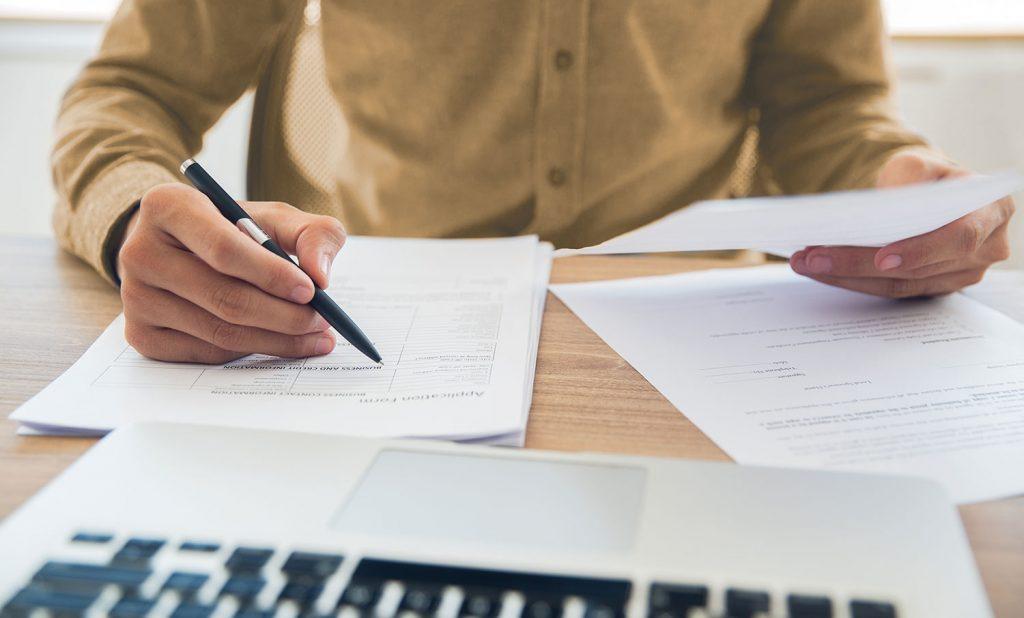 Mann schriebt auf Papierstapel vor einem Macbook