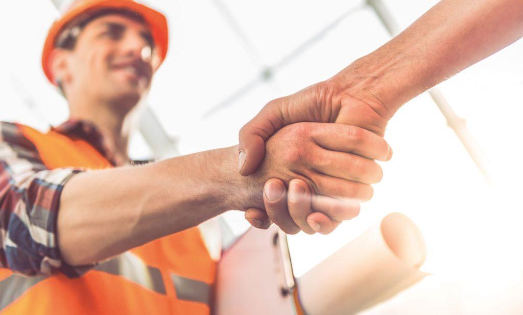 Handschlag von einem Mann mit orangener Warnweste und orangenem Helm