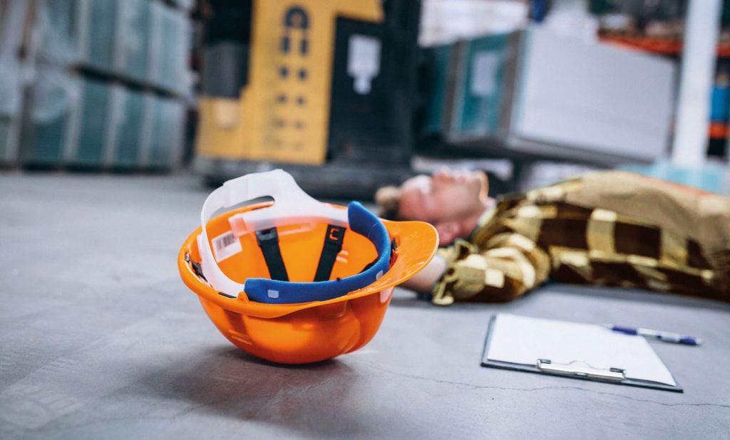 im Hintergrund liegt ein Mann auf dem Boden, im Vordergrund liegt ein orangener Helm und ein Klemmbrett mit Stift