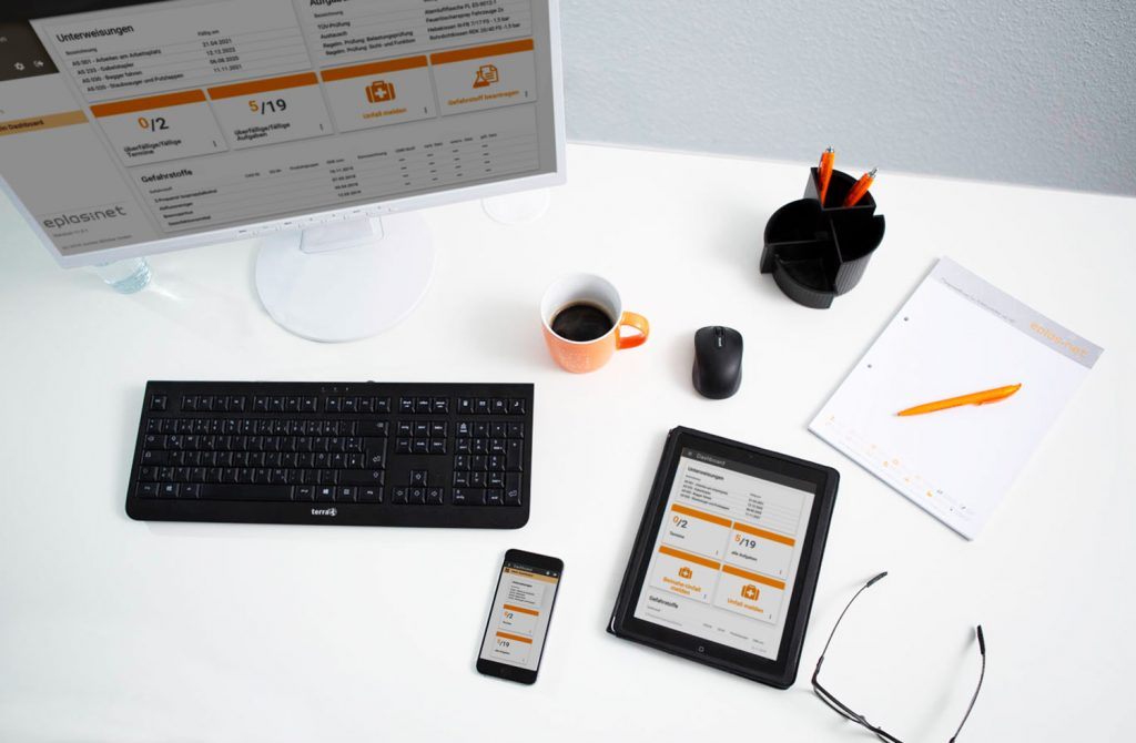 Schreibtisch von oben mit Bildschirm eplas Dashboard, Tastatur, Kaffeetasse, mouse, Block mit Stiften, Brille Tablet mit eplas Dashboard und Handy mit Dashboardansicht von eplas